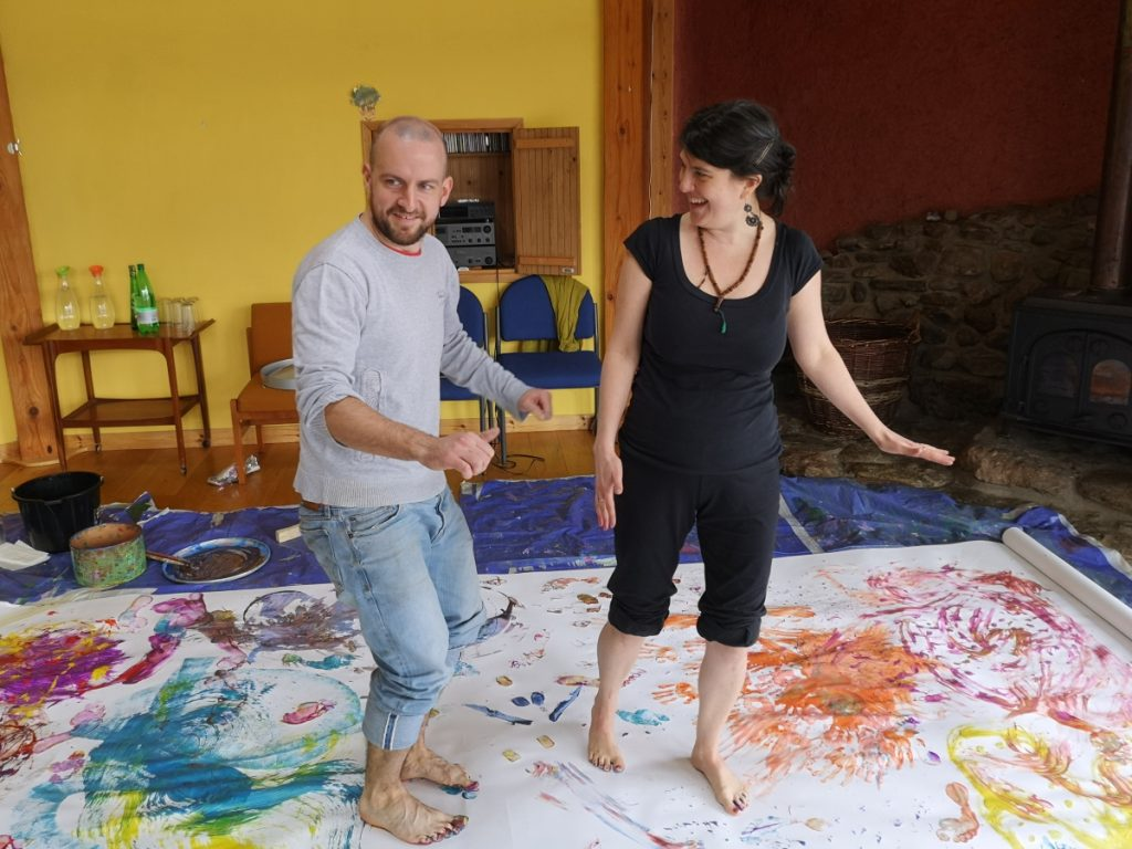 Two adults create an artwork using their painted feet